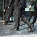 Mannen in pak gaan een kantoor op de Zuidas binnen