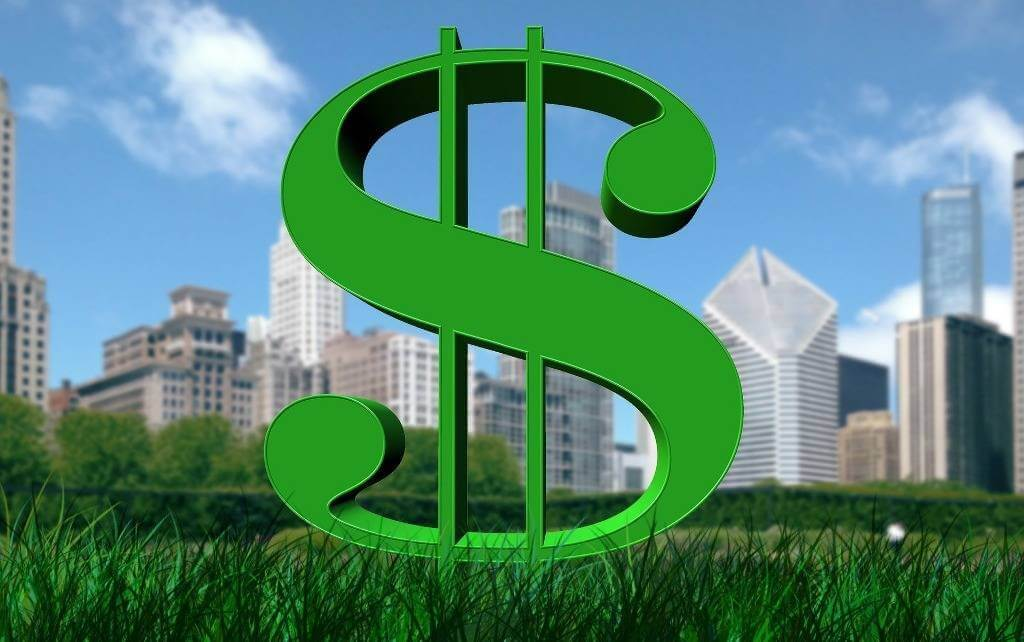 dollar sign in grass with high rise buildings in the background