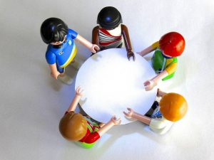 playmobile figures sitting around a round table